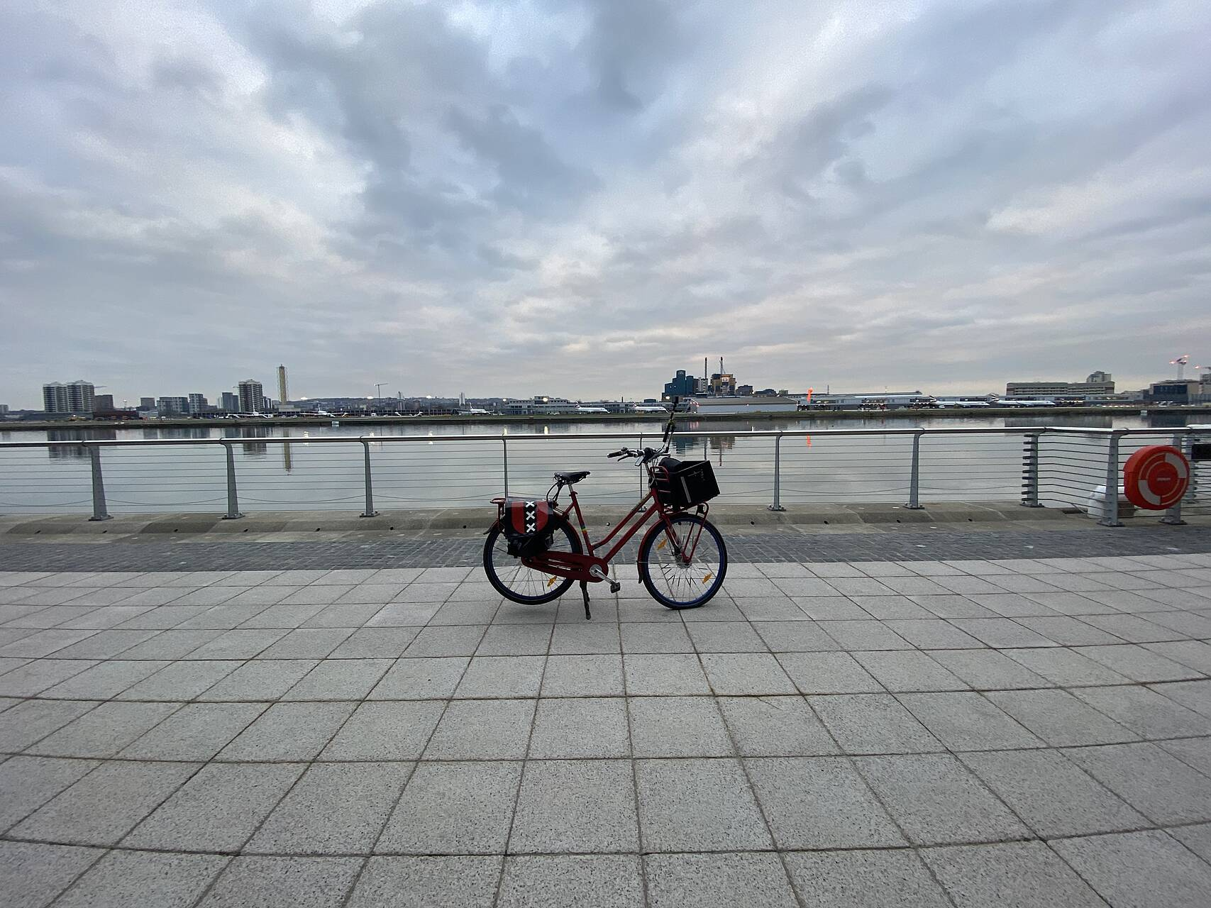 Red Dutch bicycle on its kickstand on a paved area in front of a dock with London City Airport in the background across the dock.jpeg